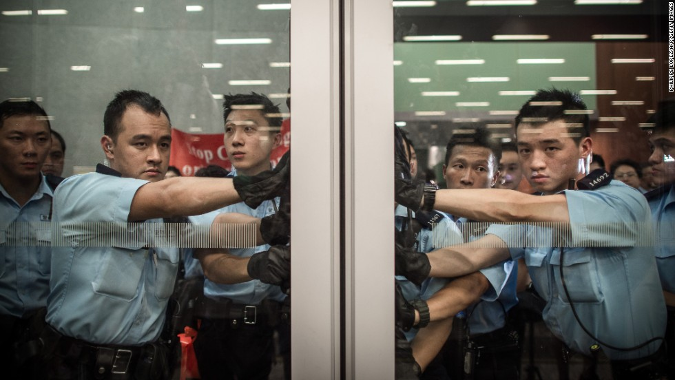 Policemen block a door of the Legislative Council in Hong Kong on Friday, June 13. Riot police were deployed to prevent protesters from gaining access to the Legislative Council and forcing the Hong Kong government to withdraw a development plan that would turn farmland into housing estates in the city's northeastern New Territories.