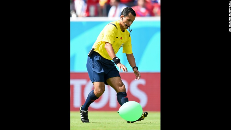Referee Enrique Osses tries to catch a balloon that came onto the field.