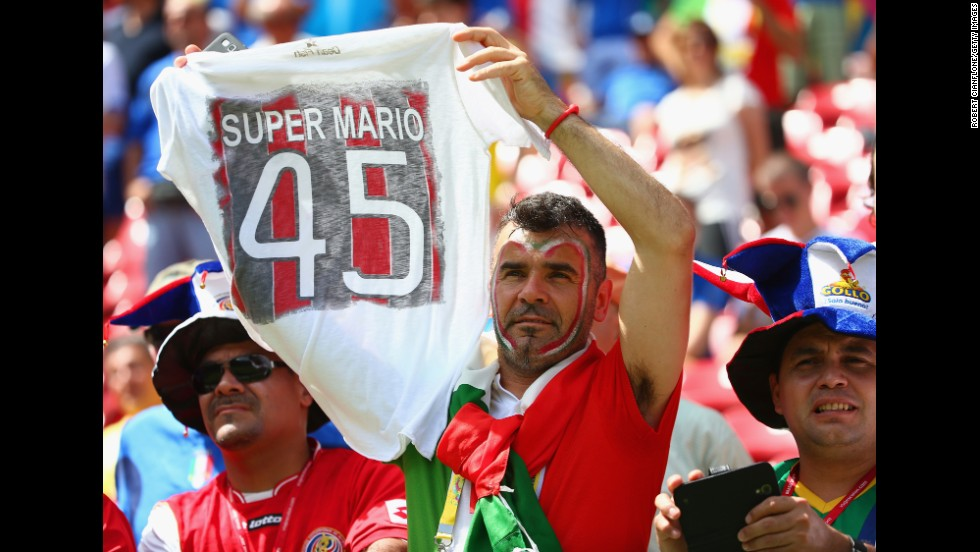 "An Italy fan holds up a T-shirt honoring Balotelli before the match. <a href=""http://www.cnn.com/2014/06/19/football/gallery/world-cup-0619/index.html"">See the best World Cup photos from June 19.</a>"