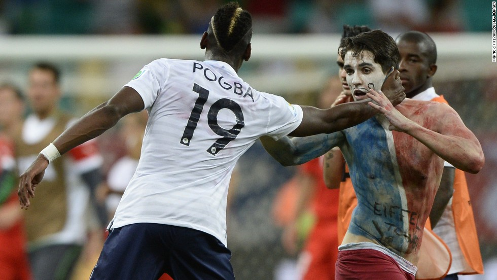 French midfielder Paul Pogba reaches out to a team supporter who ran onto the field at the end of France's World Cup match against Switzerland in Salvador, Brazil. France thrashed Switzerland 5-2 to go atop Group E.