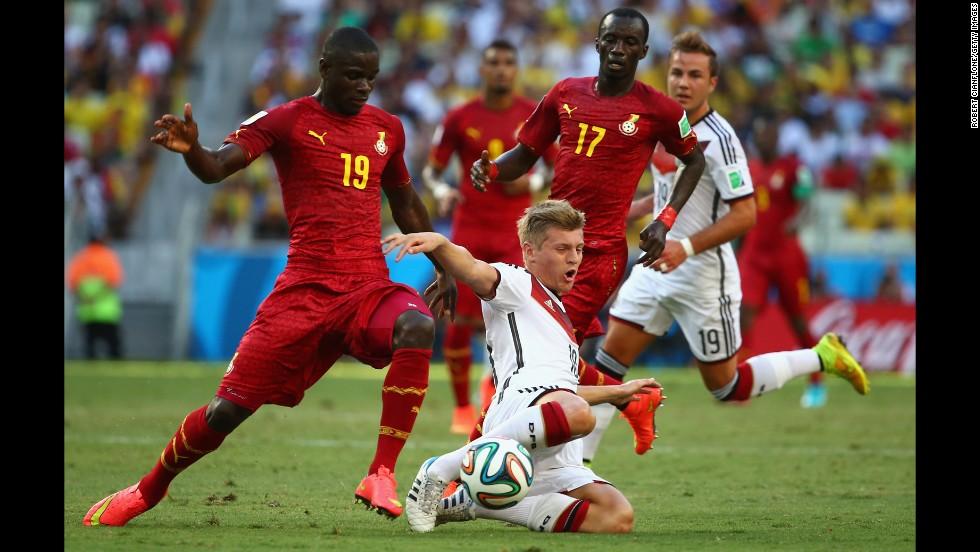 Toni Kroos of Germany is challenged by Jonathan Mensah, left,  and Mohammed Rabiu of Ghana.
