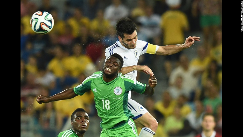 Nigeria forward Michael Babatunde jumps to head the ball with Bosnia-Herzegovina defender and captain Emir Spahic.