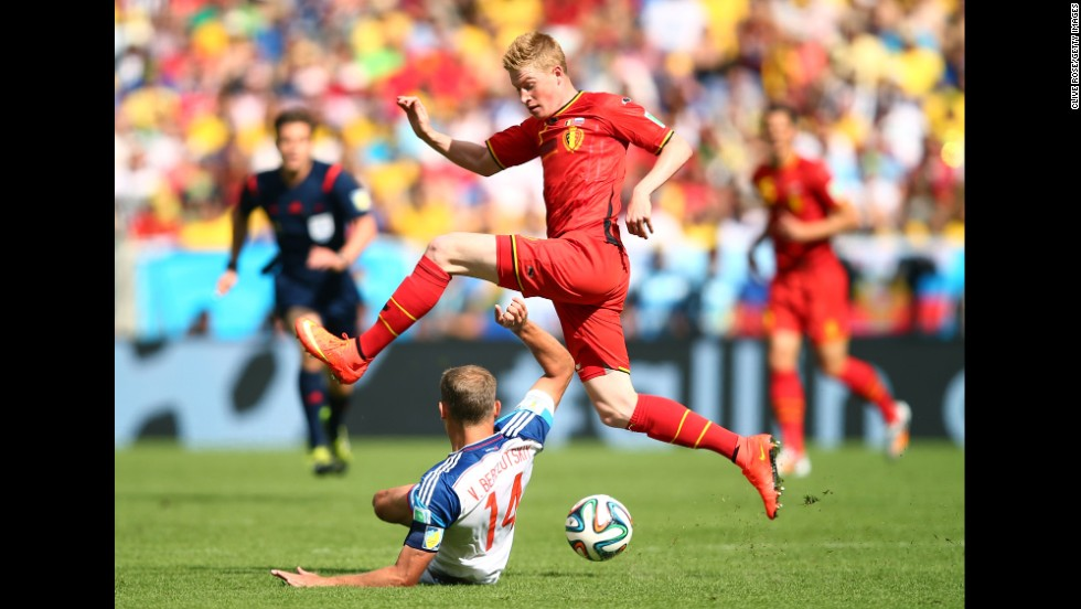 Kevin De Bruyne of Belgium tries to dodge a tackle by Vasily Berezutskiy of Russia.