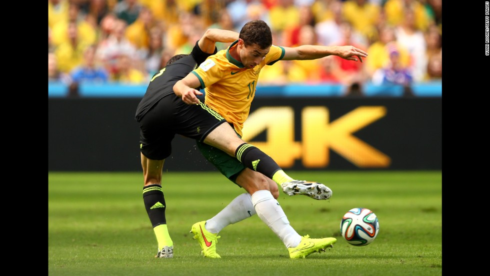 Australia's Oar is challenged by Spain's Juanfran.
