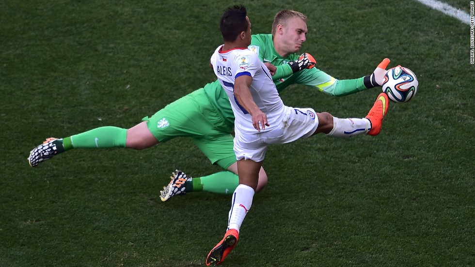 Chile forward Alexis Sanchez, front, competes for the ball with Netherlands goalkeeper Jasper Cillessen.