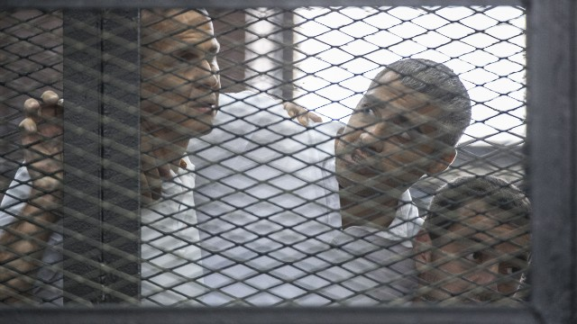 Al-Jazeera news channel's Australian journalist Peter Greste (L) and his colleagues, Egyptian-Canadian Mohamed Fadel Fahmy (C) and Egyptian Baher Mohamed , listen to the verdict inside the defendants cage during their trial for allegedly supporting the Muslim Brotherhood on June 23, 2014 at the police institute near Cairo's Tora prison.