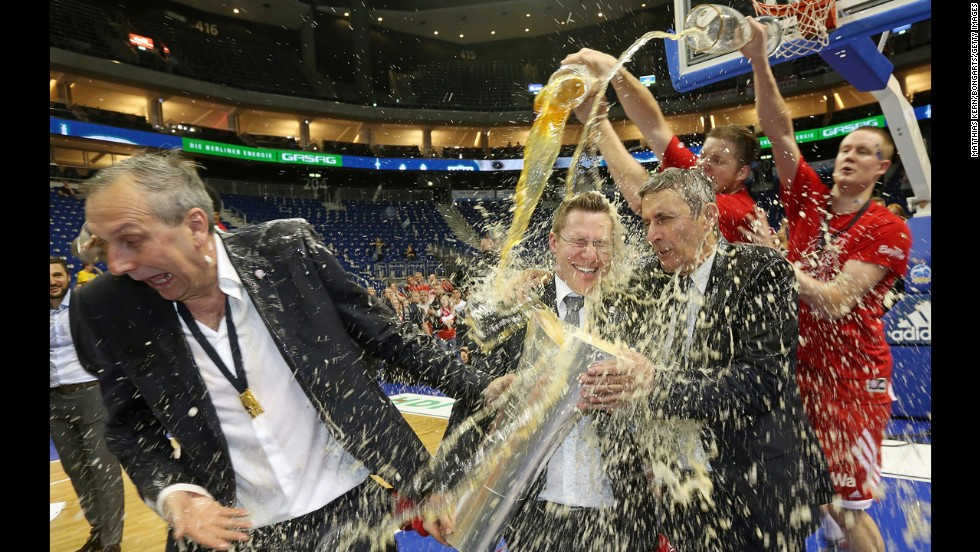 From left, assistant coaches Emir Mutapcic and Andreas Wagner and head coach Svetislav Pesic of Bayern Munich get a beer shower after beating Alba Berlin the Beko BBL basketball playoffs on Wednesday, June 18, in Berlin.