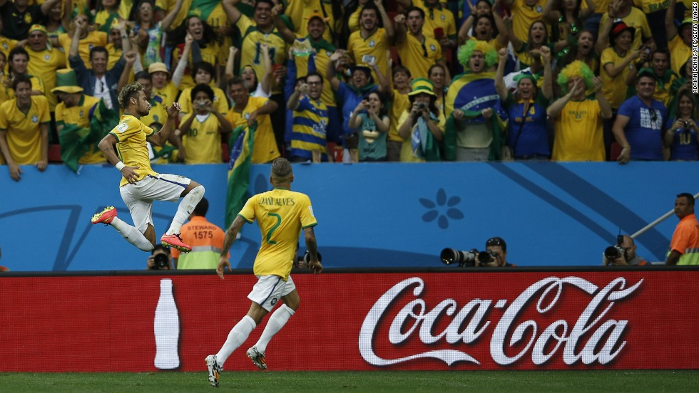 Brazil forward Neymar, left, celebrates with his teammate Dani Alves after scoring Brazil's second goal against Cameroon.