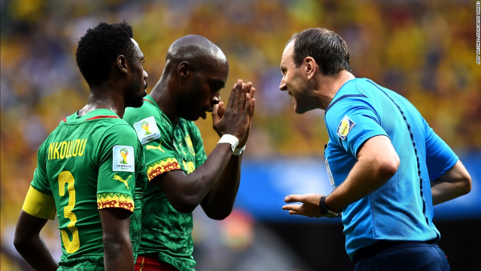 Referee Jonas Eriksson, right, speaks to Allan Nyom, center, of Cameroon.