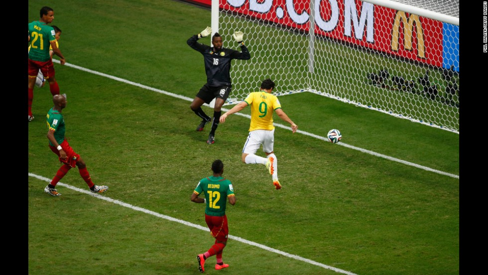 Fred of Brazil scores his team's third goal on a header past Charles Itandje of Cameroon.