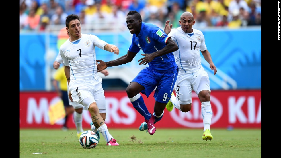 Mario Balotelli of Italy competes for the ball against Cristian Rodriguez, left, and Egidio Arevalo Rios, right, of Uruguay.