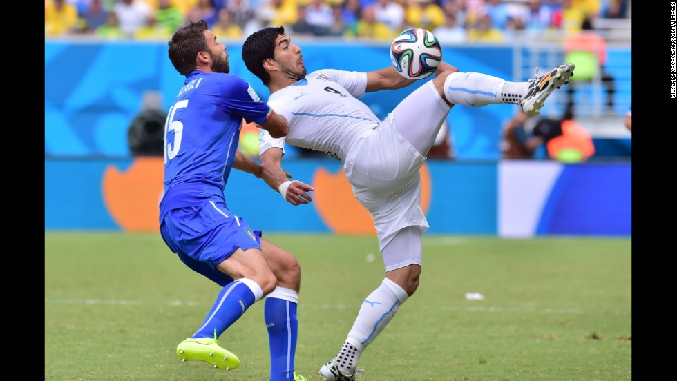 Italy defender Andrea Barzagli, left, and Uruguay forward Luis Suarez vie for the ball.