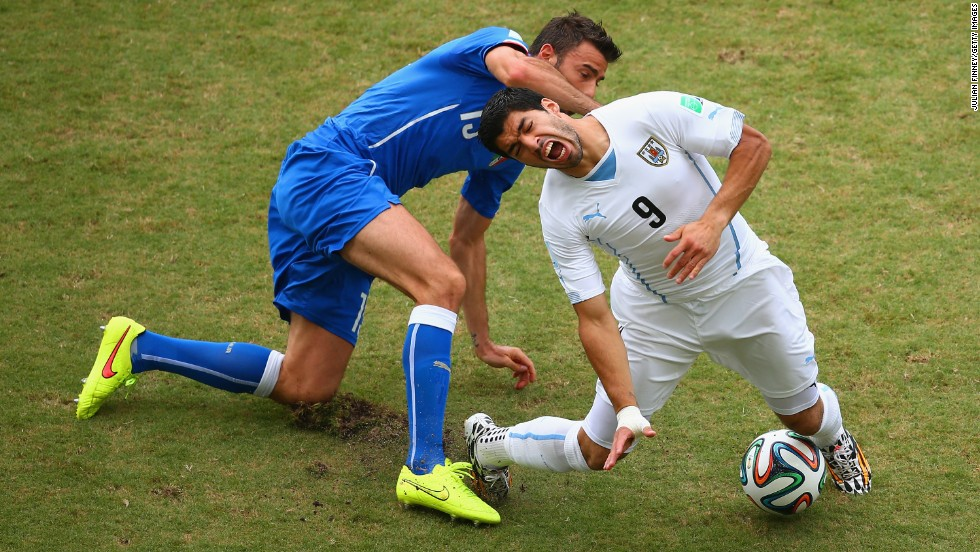 Andrea Barzagli of Italy challenges Luis Suarez of Uruguay.