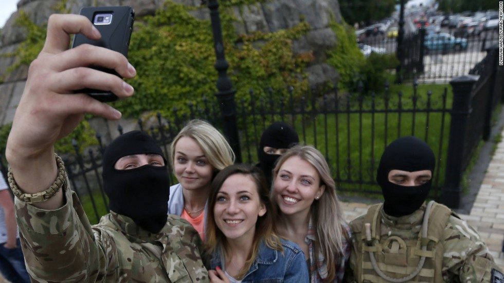 "Masked volunteers who have joined an army battalliot for the Ukrainian government pose for a selfie with their girlfriends after taking an oath of allegiance in central Kiev, on Monday, June 23. <a href=""http://www.cnn.com/2014/06/18/world/gallery/look-at-me-0618/index.html"">See 17 selfies from last week</a>"