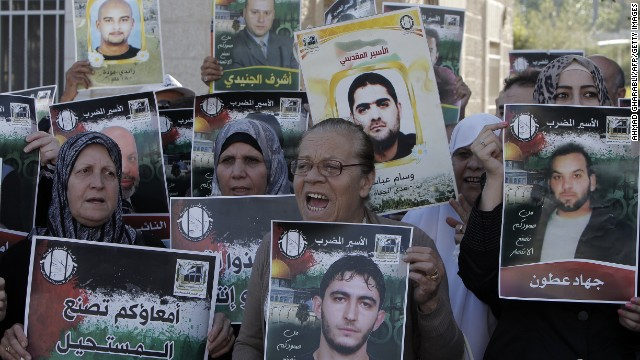 Palestinians hold up images of relatives as they demonstrate to show solidarity with hunger-striking Palestinian prisoners held by Israel, outside the Red Cross building in east Jerusalem on June 12, 2014. Some 285 Palestinian prisoners are observing a mass hunger strike in protest against their being held without charge under a procedure called administrative detention. Of that number, 125 have been refusing food for more than six weeks, with 65 of them being treated in hospital, according to the Israeli Prisons Service. AFP PHOTO/AHMAD GHARABLI (Photo credit should read AHMAD GHARABLI/AFP/Getty Images)