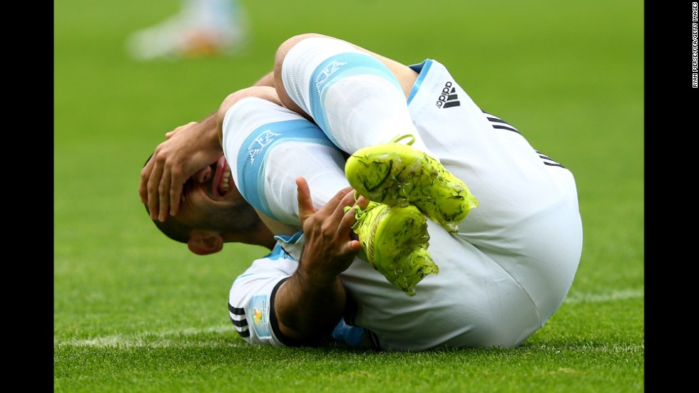 Javier Mascherano of Argentina falls to the ground wincing.