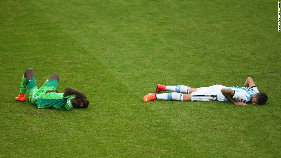 Juwon Oshaniwa of Nigeria and Ricardo Alvarez of Argentina lie on the field after a collision.