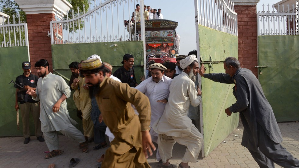 Displaced Pakistanis force their way into a food distribution center.