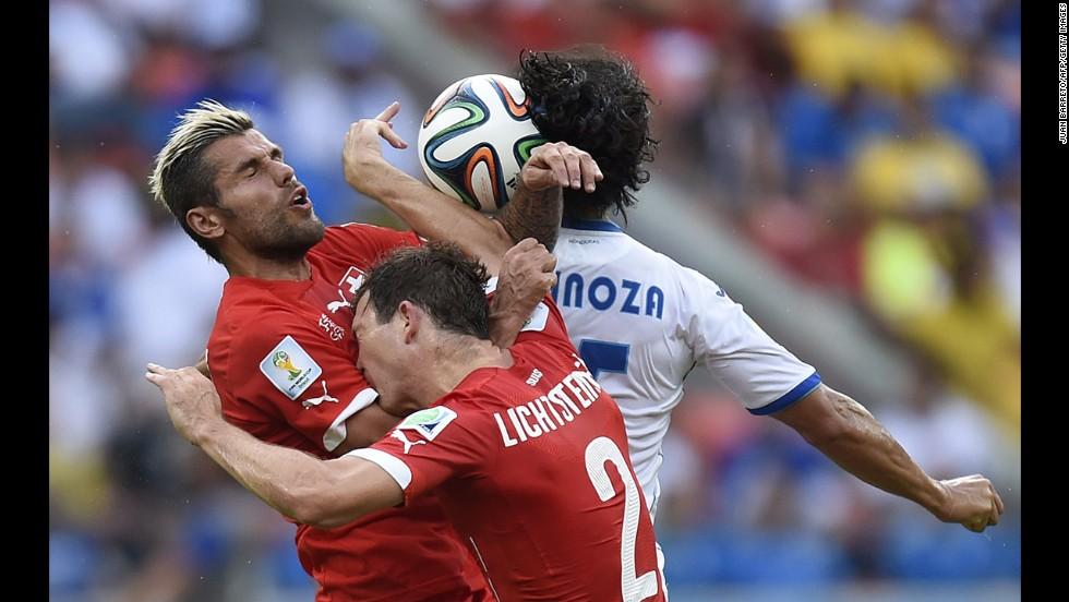 Honduras midfielder Roger Espinoza, back, jumps to head the ball with Switzerland midfielder Valon Behrami, left, and defender Stephan Lichtsteiner.