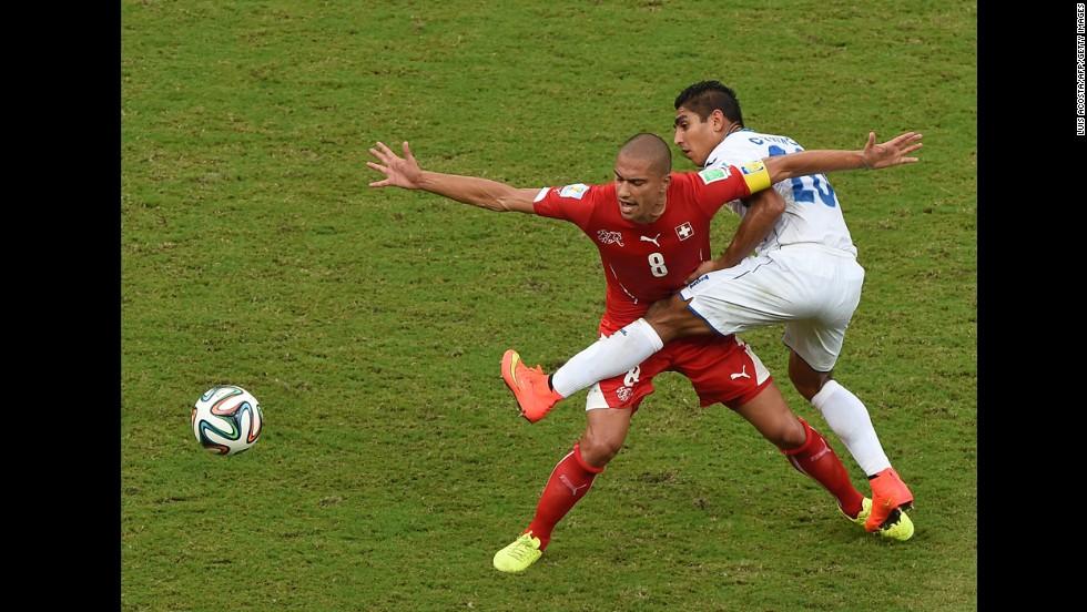 Honduras midfielder Jorge Claros, right, challenges Switzerland midfielder Goekhan Inler.
