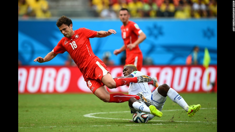 Admir Mehmedi of Switzerland is tackled by Brayan Beckeles of Honduras.