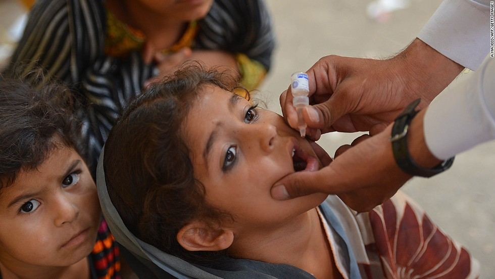 A Pakistani health worker gives a dose of polio vaccine to a child in Bannu on June 25. The World Health Organization has launched a campaign to stop the spread of the illness as hundreds of thousands of people flee North Waziristan.