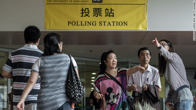People get information outside a polling station in Hong Kong on June 22, 2014. Physical booths opened for Hong Kong's unofficial referendum on democratic reform after more than half a million had voted online, as Beijing warned the vote is illegal. AFP PHOTO / Philippe Lopez (Photo credit should read PHILIPPE LOPEZ/AFP/Getty Images)