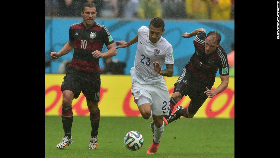 Lukas Podolski and Benedikt Hoewedes of Germany chase after Fabian Johnson of the United States.