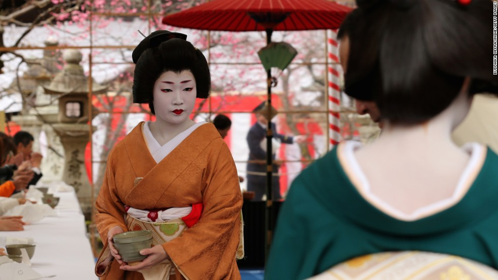 A full-fledged geisha serves tea during Kyoto's annual Plum Blossom Festival. Aside from their regular hosting engagements, trained geisha are often hired to perform at local festivals.