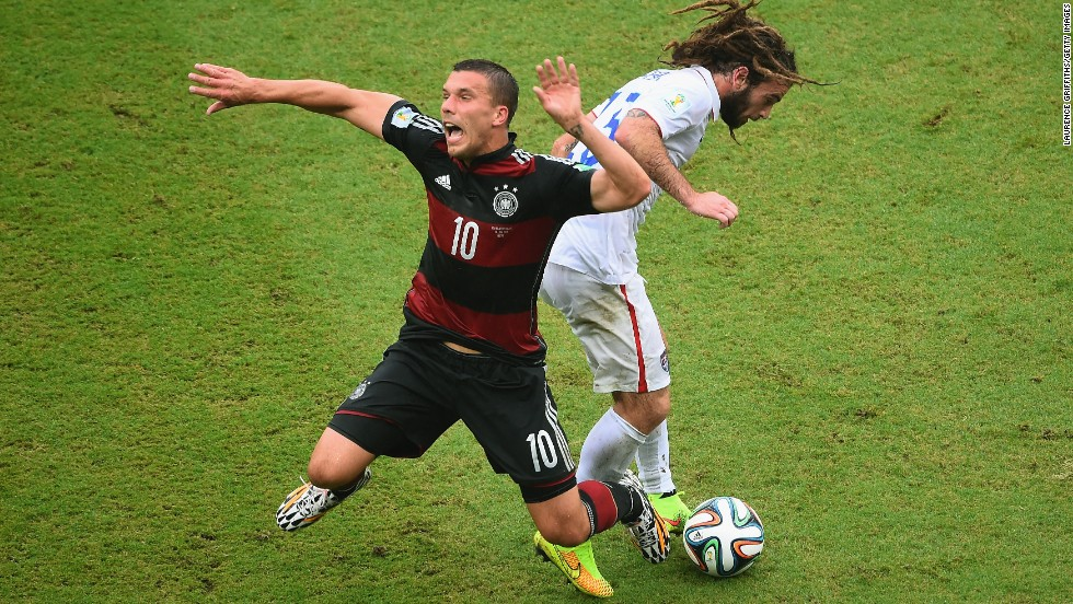 Lukas Podolski of Germany is challenged by Kyle Beckerman of the United States.