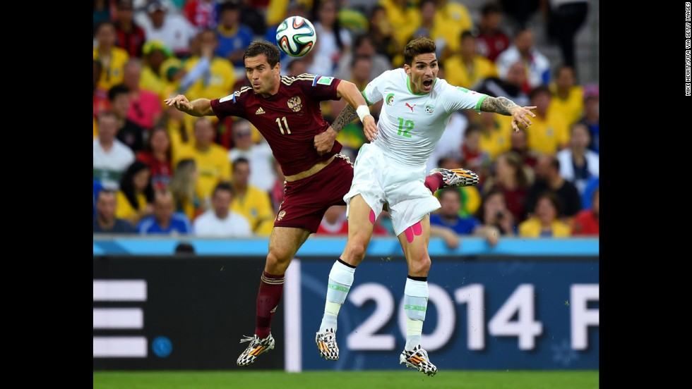 Aleksandr Kerzhakov of Russia and Carl Medjani of Algeria compete for the ball.