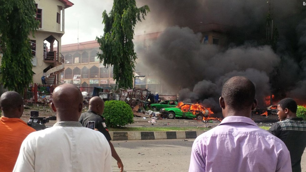 Onlookers watch smoke fill the sky after an explosion at a shopping mall in Abuja, Nigeria, on Wednesday, June 25. The blast killed 21 people and injured 52 others, authorities said.