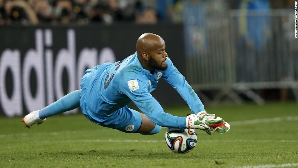 Algeria's goalkeeper Rais M'bohli dives for the ball.