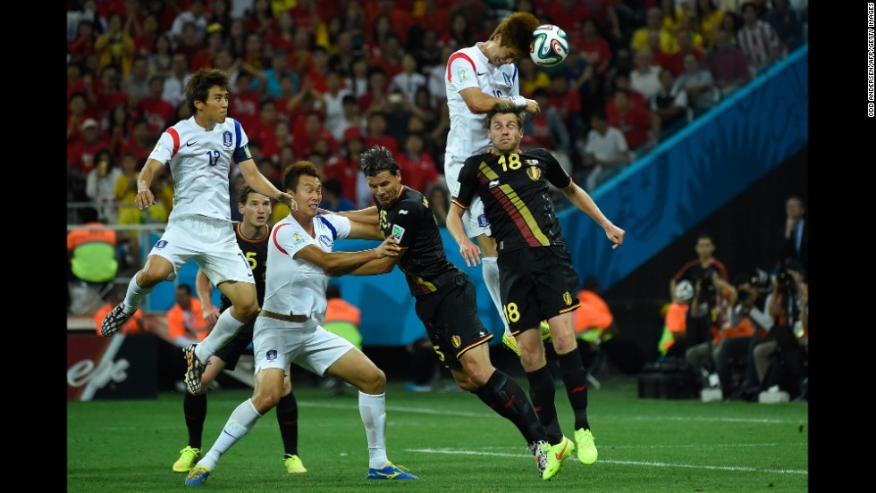 South Korea midfielder Ki Sung-Yueng, second right, heads the ball.