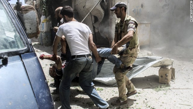 Rebel fighters aid injured civilians following reported shelling by regime forces on Jobar, on the outskirt of Damascus on June 26, 2014