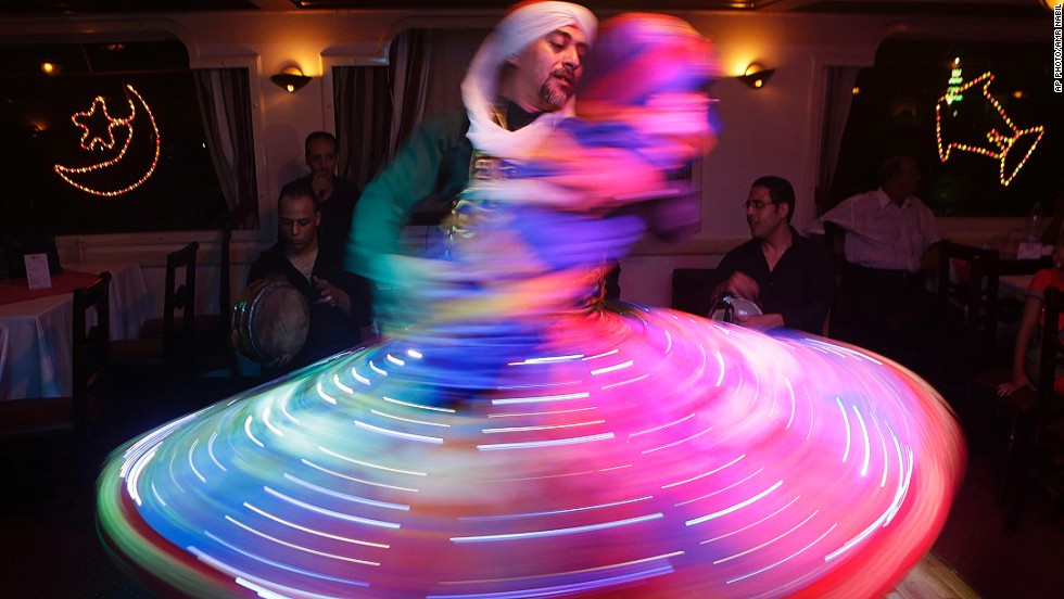 "JUNE 27 - CAIRO, EGYPT: An Egyptian dancer wearing a traditional costume performs while pretending to hold a baby in his arms during a night show marking the holy month of Ramadan on June 26. The dance is locally known as ""whirling dervish."" Muslims observe the dawn-to-dusk fasting starting this weekend."