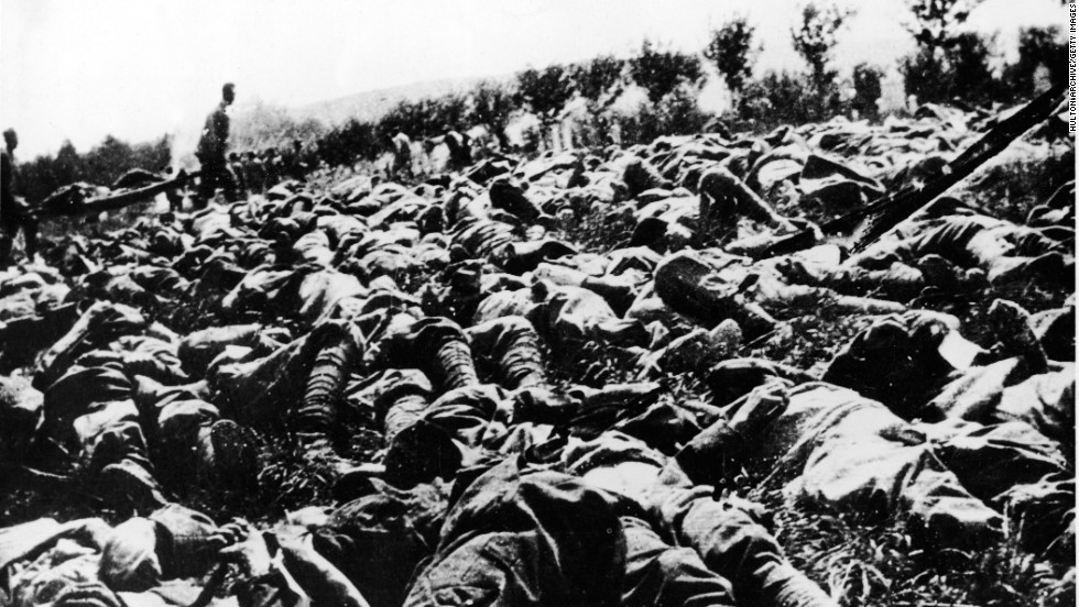 The bodies of hundreds of Italian soldiers are strewn across the battlefield, victims of a gas and flame attack during World War I, as others haul the wounded on stretchers. They were members of the Ninth Italian Regiment of the Queen's Brigade.