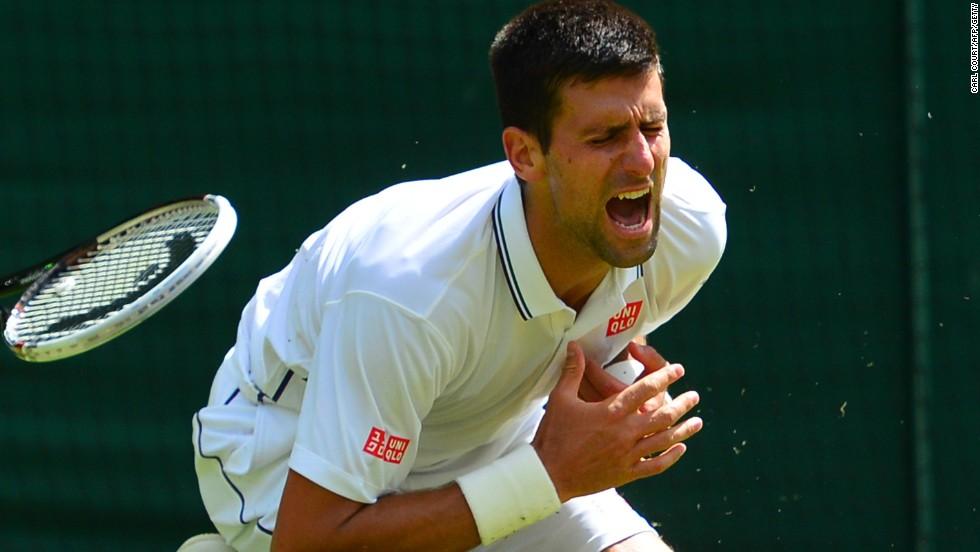 Novak Djokovic clutches his shoulder after an awkward fall during his third round match at Wimbledon.