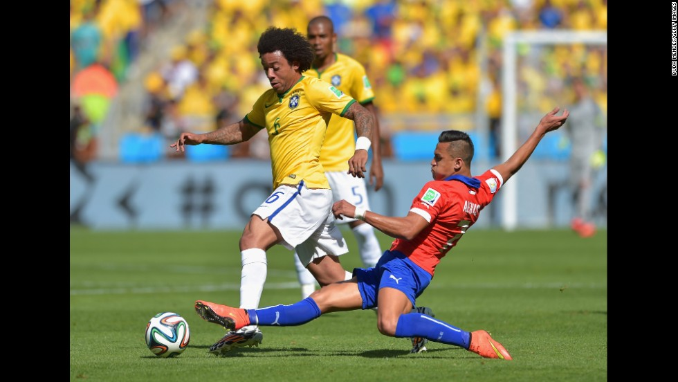 Alexis Sanchez of Chile tackles Marcelo of Brazil.