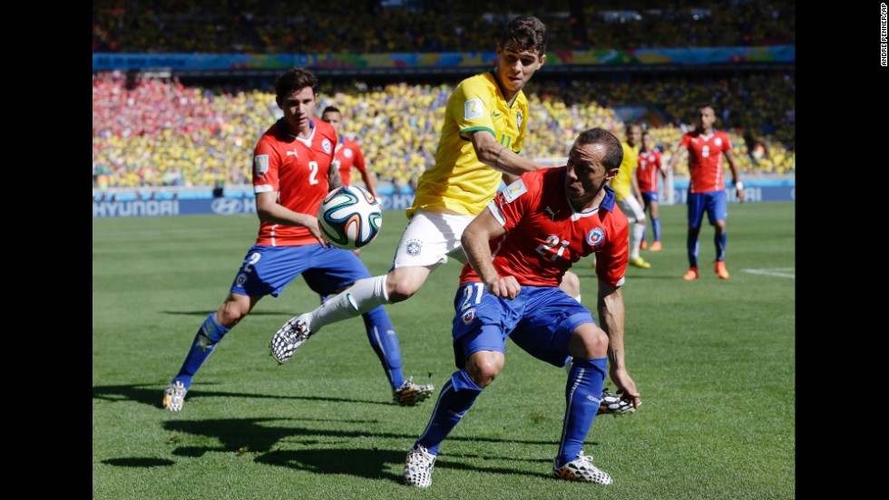 Brazil's Oscar, center, is challenged by Chile's Marcelo Diaz, right, on June 26.