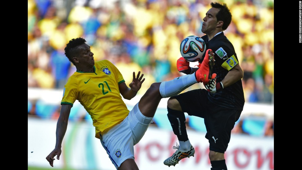 Jo of Brazil tries to score a goal as Chile's goalkeeper Claudio Bravo saves the ball.