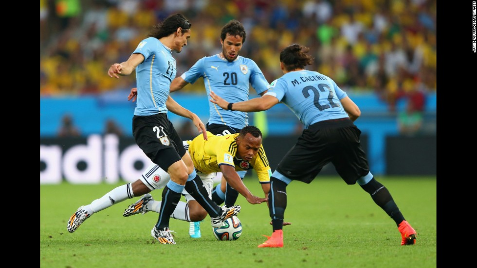 Juan Camilo Zuniga of Colombia is challenged by a trio of players from Uruguay.