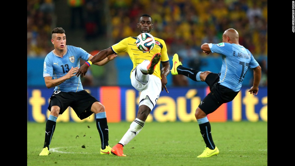 Jackson Martinez of Colombia controls the ball against Jose Gimenez, left, and Egidio Arevalo Rios of Uruguay.