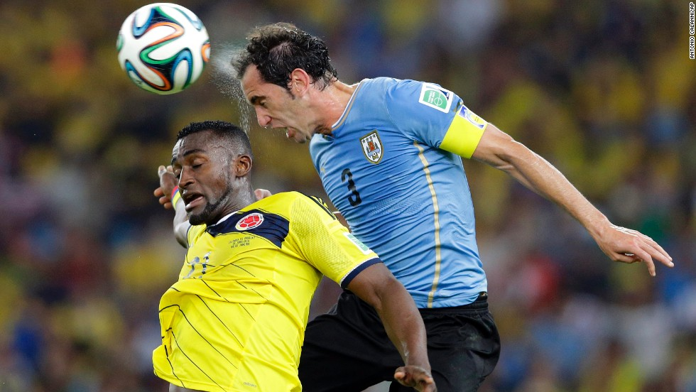 Colombia's Jackson Martinez and Uruguay's Diego Godin jump for the ball.