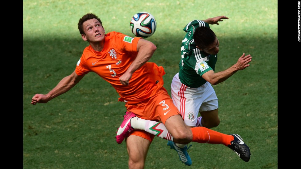 Stefan de Vrij of the Netherlands, in orange, challenges Oribe Peralta of Mexico for the ball during a World Cup game between the two nations in Fortaleza, Brazil, on Sunday, June 29.