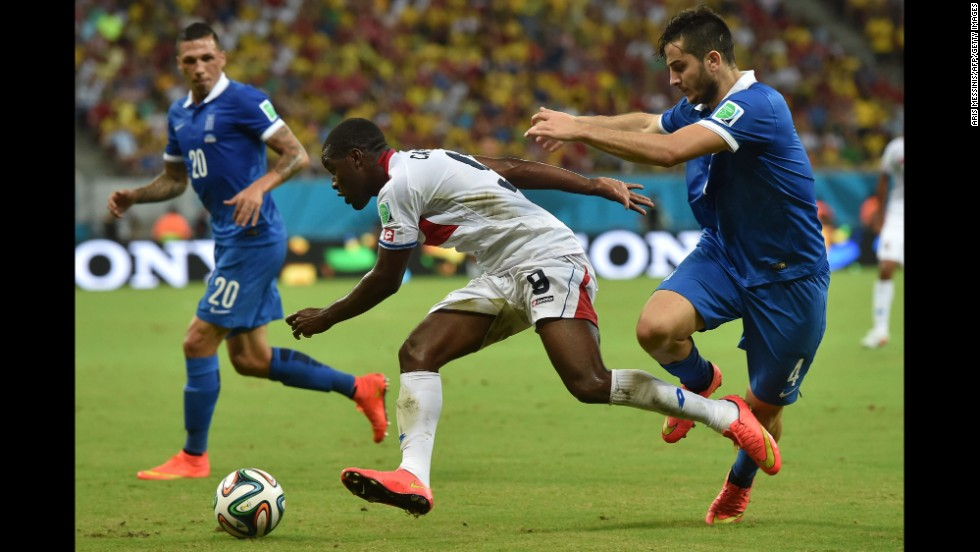 Joel Campbell of Costa Rica, center, dribbles past Konstantinos Manolas of Greece.