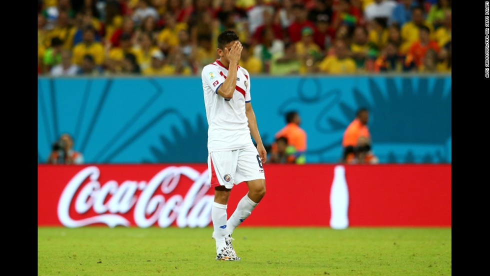 Oscar Duarte of Costa Rica walks off the pitch after being shown a red card, taking the Costa Rican team down to 10 men against Greece.