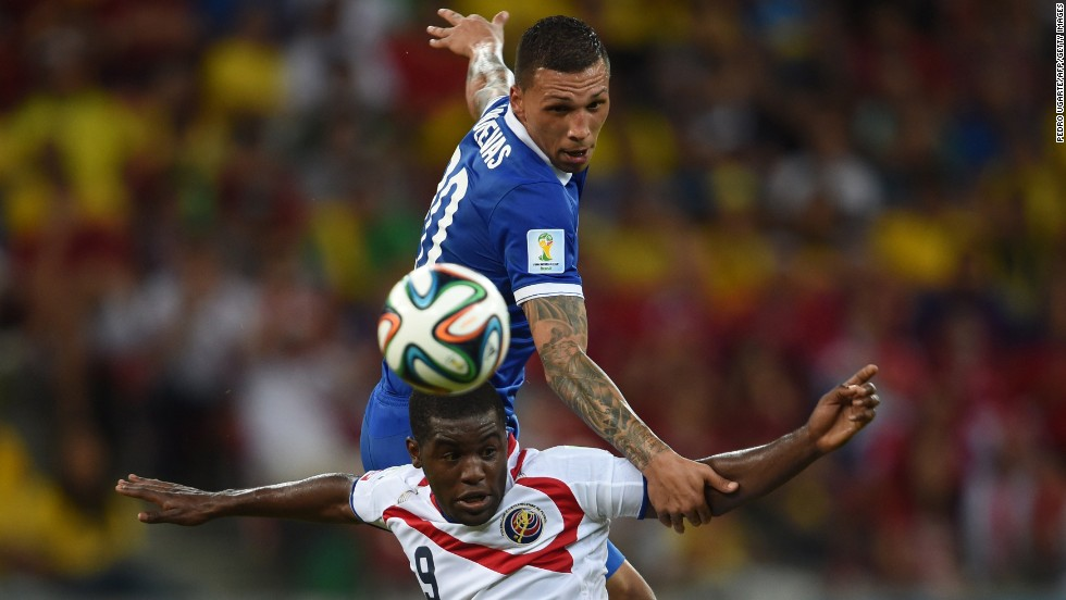 Greece's Jose Holebas jumps over Costa Rica's Joel Campbell.