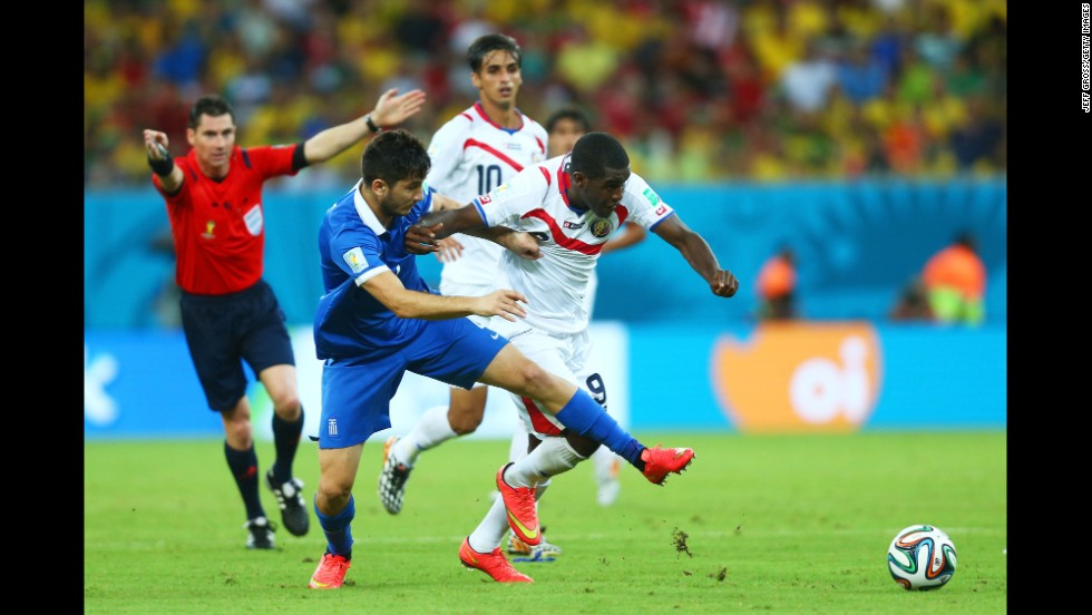 Konstantinos Manolas of Greece challenges Joel Campbell of Costa Rica.