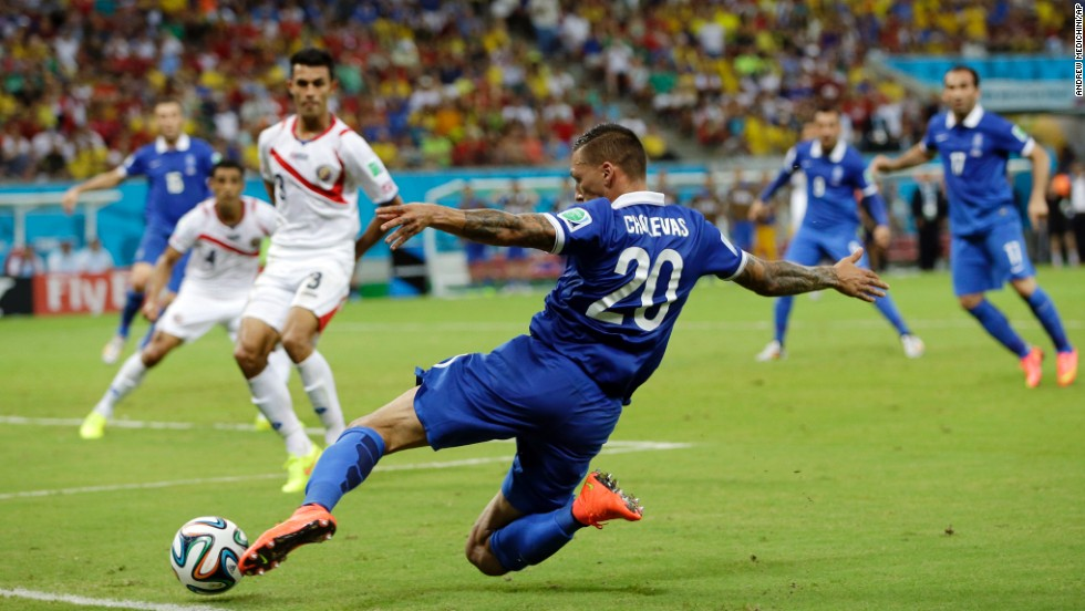 Greece's Jose Holebas runs to kick a cross during extra time before the penalty shootout.